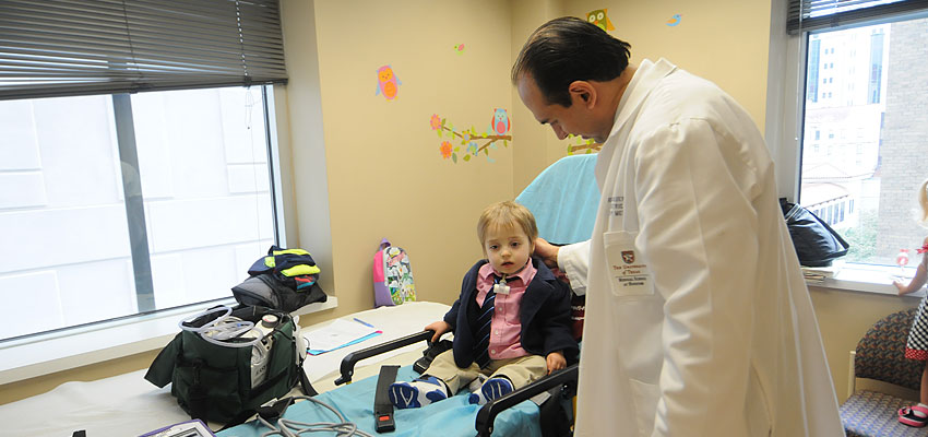 Dr. Ricardo Mosquera greets Leonard Munoz, 2, who arrives to the UT Physicians High Risk Children's Clinic via a stretcher.