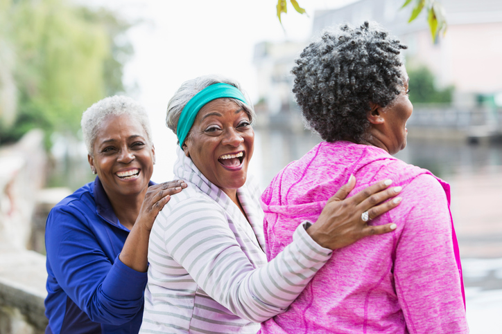 Three senior women laughing together outdoors