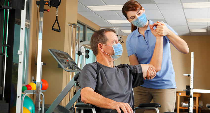 Physical Therapist And Patient In Wheelchair Wearing Protective Masks