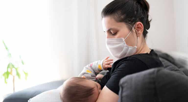 masked mom breastfeeding baby
