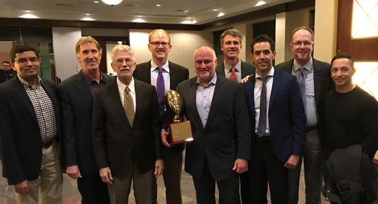"""Walter Lowe, M.D. (center) accepted the Jerry """"Hawk"""" Rhea award as the NFL's most outstanding team physician by the Professional Football Athletic Trainers Society. (Photo by Geoff Kaplan ATC, PT, SCS, CSCS, Sr. Director of Sports Medicine & Head Athletic Trainer.)"""