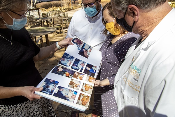 Photo of Alexis and her parents looking over a scrapbook with Fletcher. (Photo by Cody Duty/UTHealth)