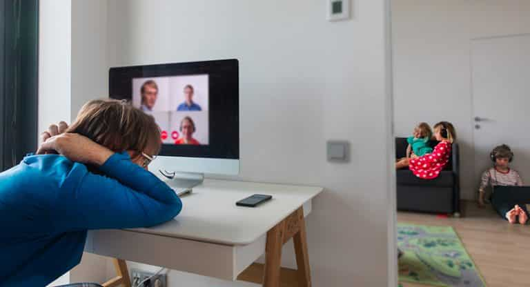 burned out father attending virtual meeting with kids in background